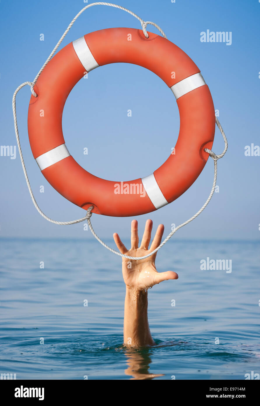 Help concept. Lifebuoy for drowning man's hand in open sea or ocean water. - Stock Image