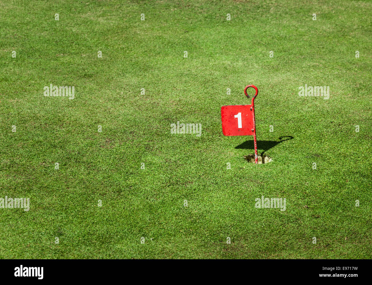 Old tin golf number one cup marker flag on a crazy golf green. - Stock Image