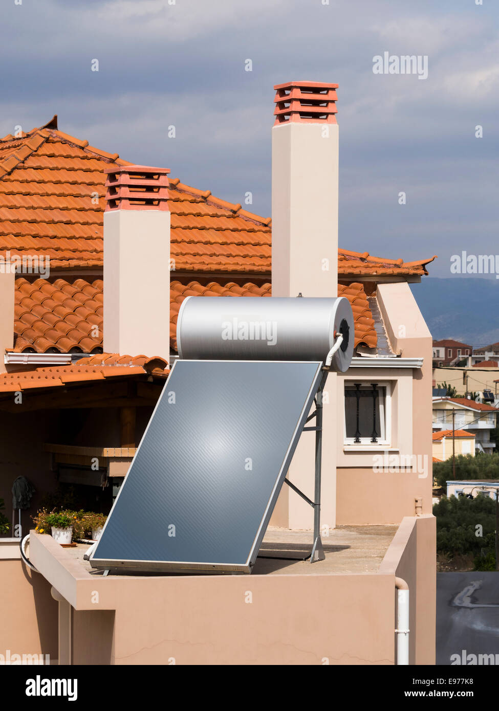Solar water heater on roof of tile roofed house - Stock Image