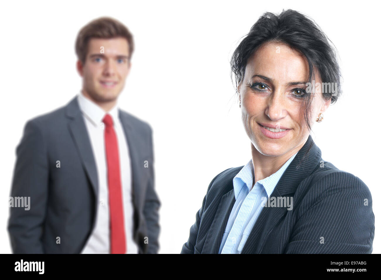 mid age business woman with younger businessman in the background - Stock Image