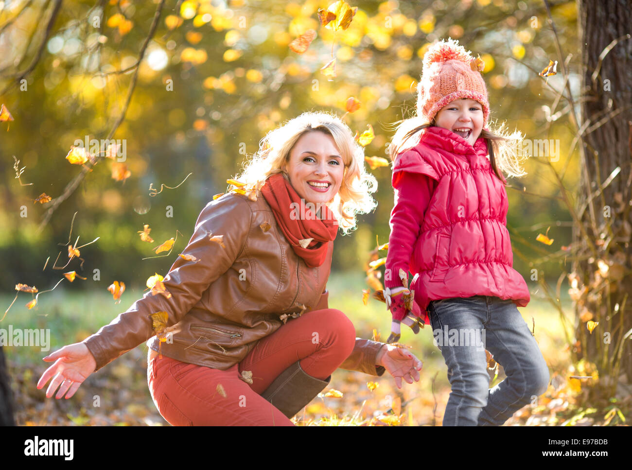 Happy parent and kid outdoor playing with autumn yellow leaves - Stock Image
