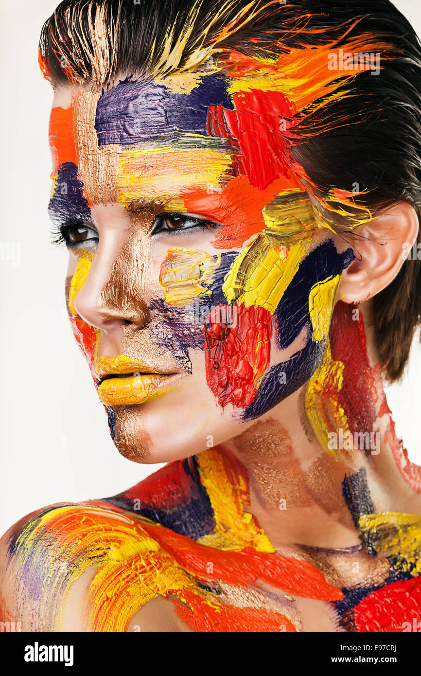 hot brunette in colourful paint - Stock Image