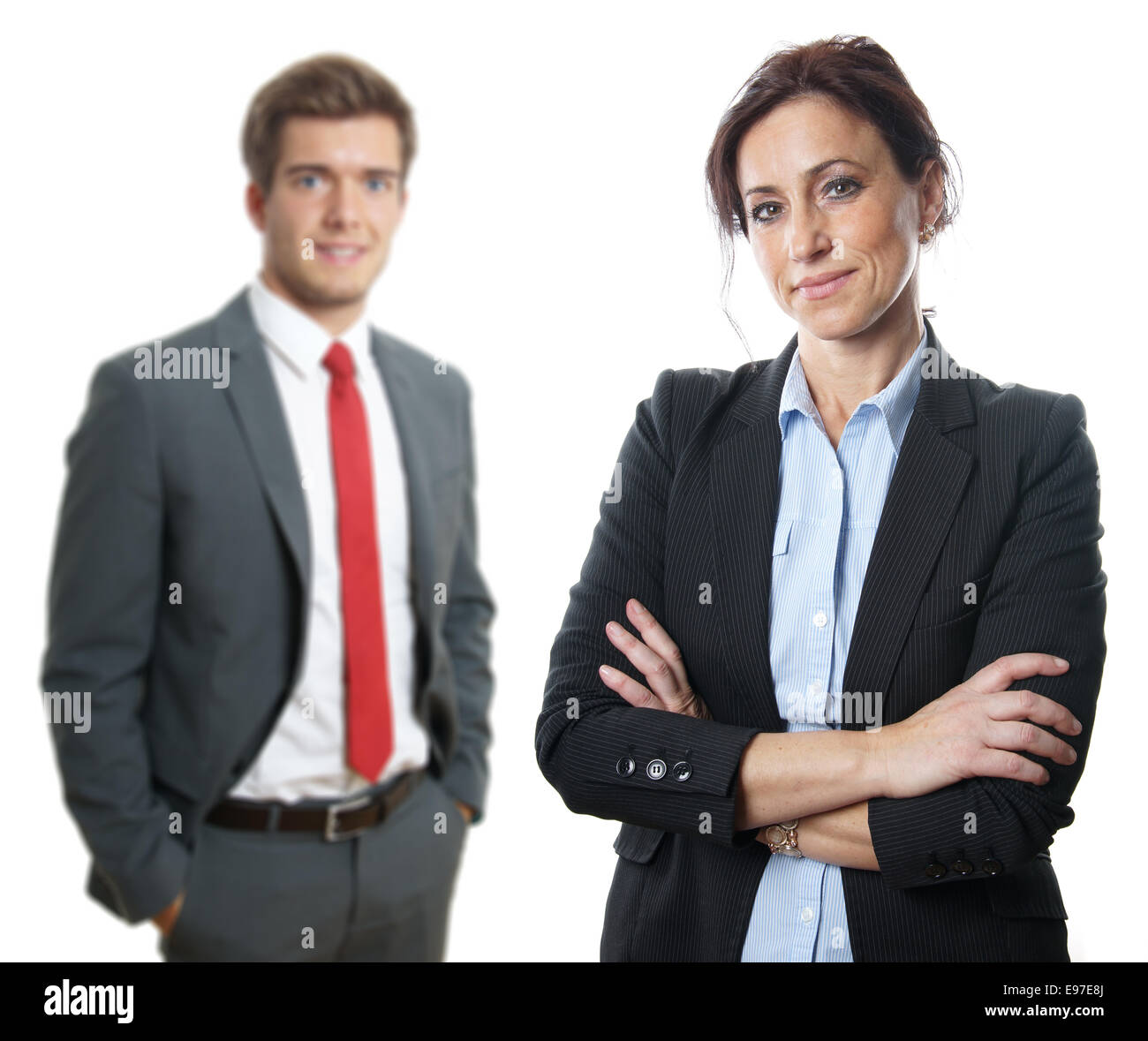 middle aged businesswoman with younger businessman in the background - Stock Image