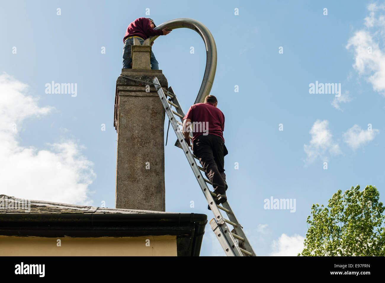 Inserting a flexible chimney liner into the chimney of an old house, UK - Stock Image