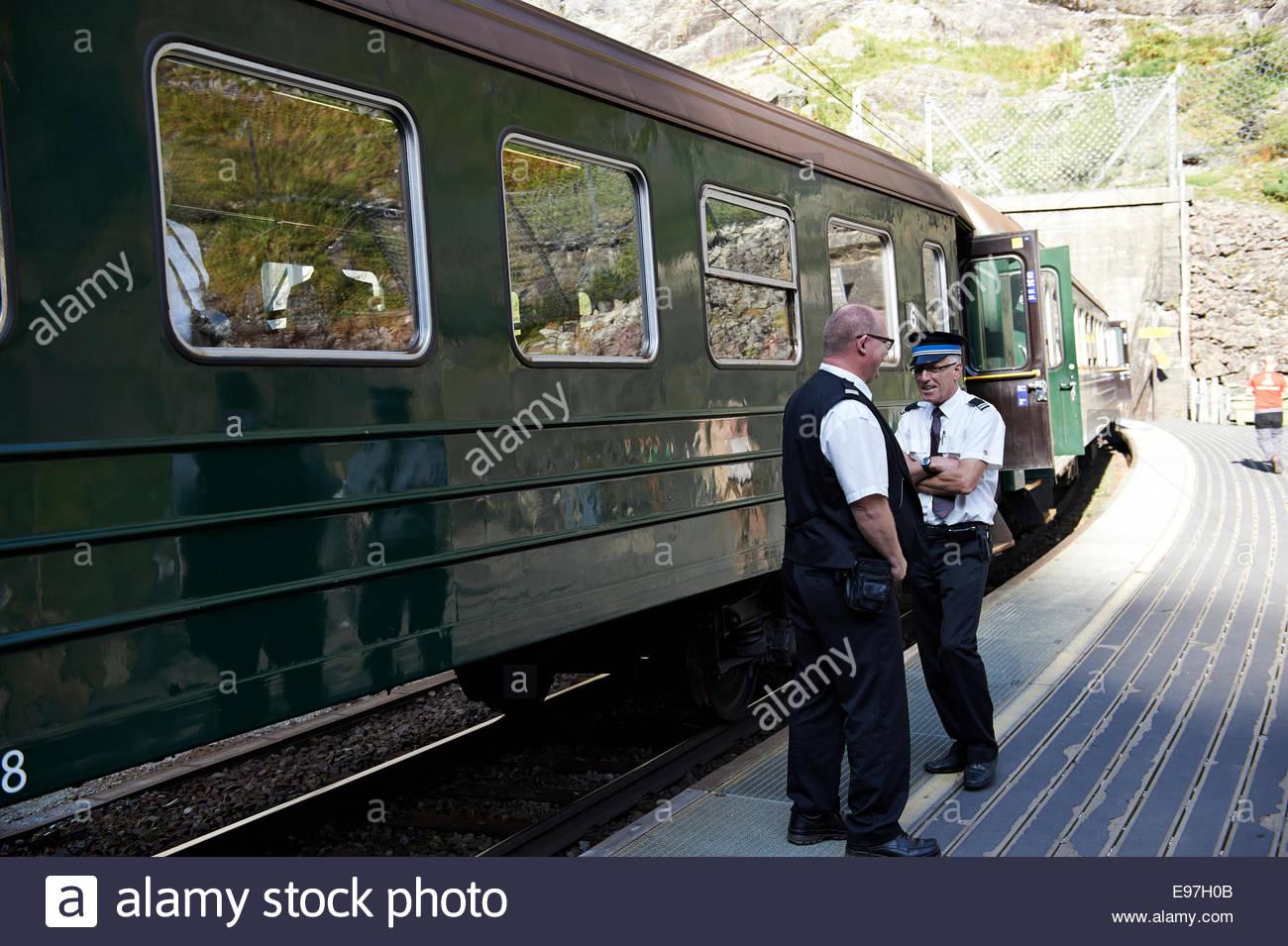 Train and Railway Officials at the Kjosfossen Waterfall Platform of the Flamsbana Railway, Flam, Aurlandsfjord, - Stock Image