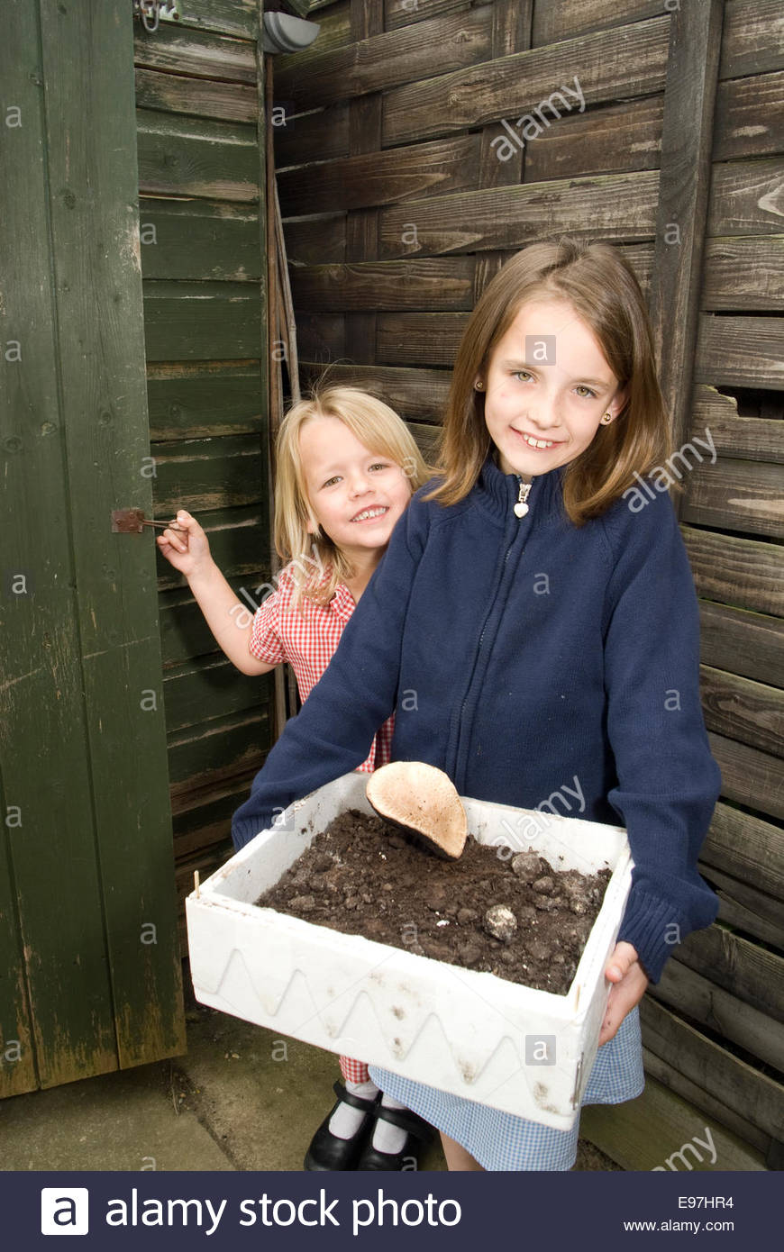Sisters learning to grow plans - Stock Image
