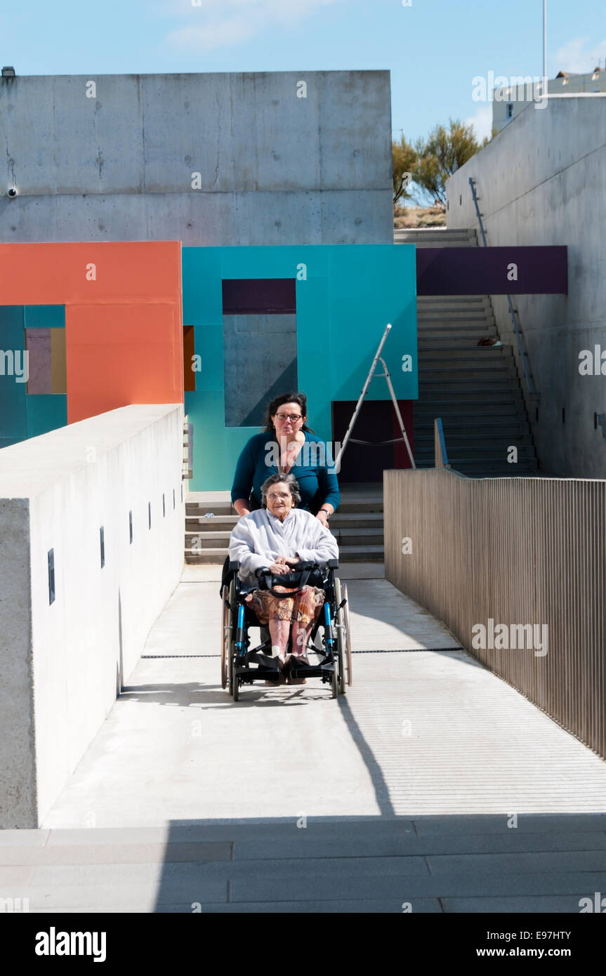An elderly lady is pushed up a concrete disabled access ramp in a wheelchair by her carer on a sunny day. - Stock Image