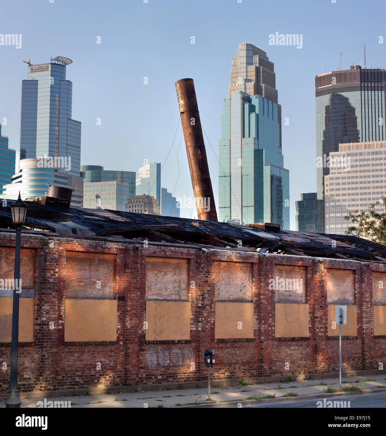 Old brick building with leaning smokestack in the historic Warehouse District with skyscrapers of downtown Minneapolis, - Stock Image