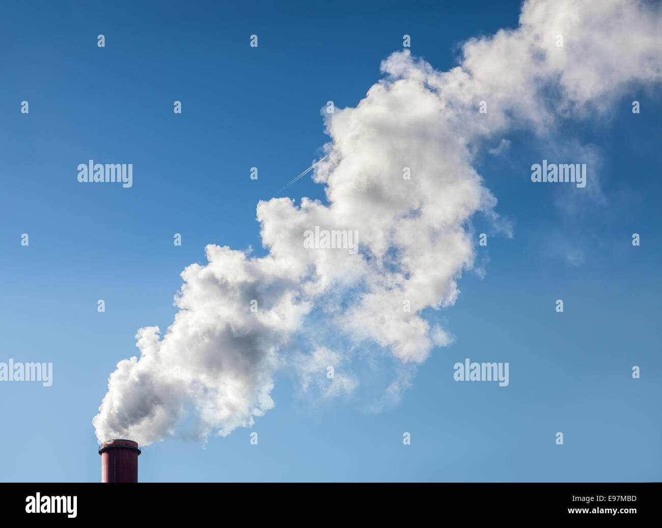 Smoke from industrial smokestack on a clear blue sky. - Stock Image
