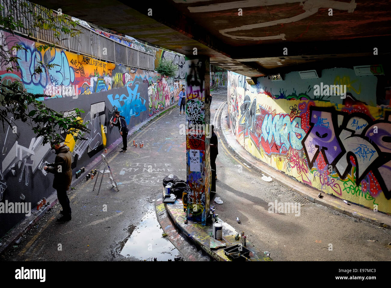 Graffiti artists decorating a wall in Leake Street in Waterloo. - Stock Image