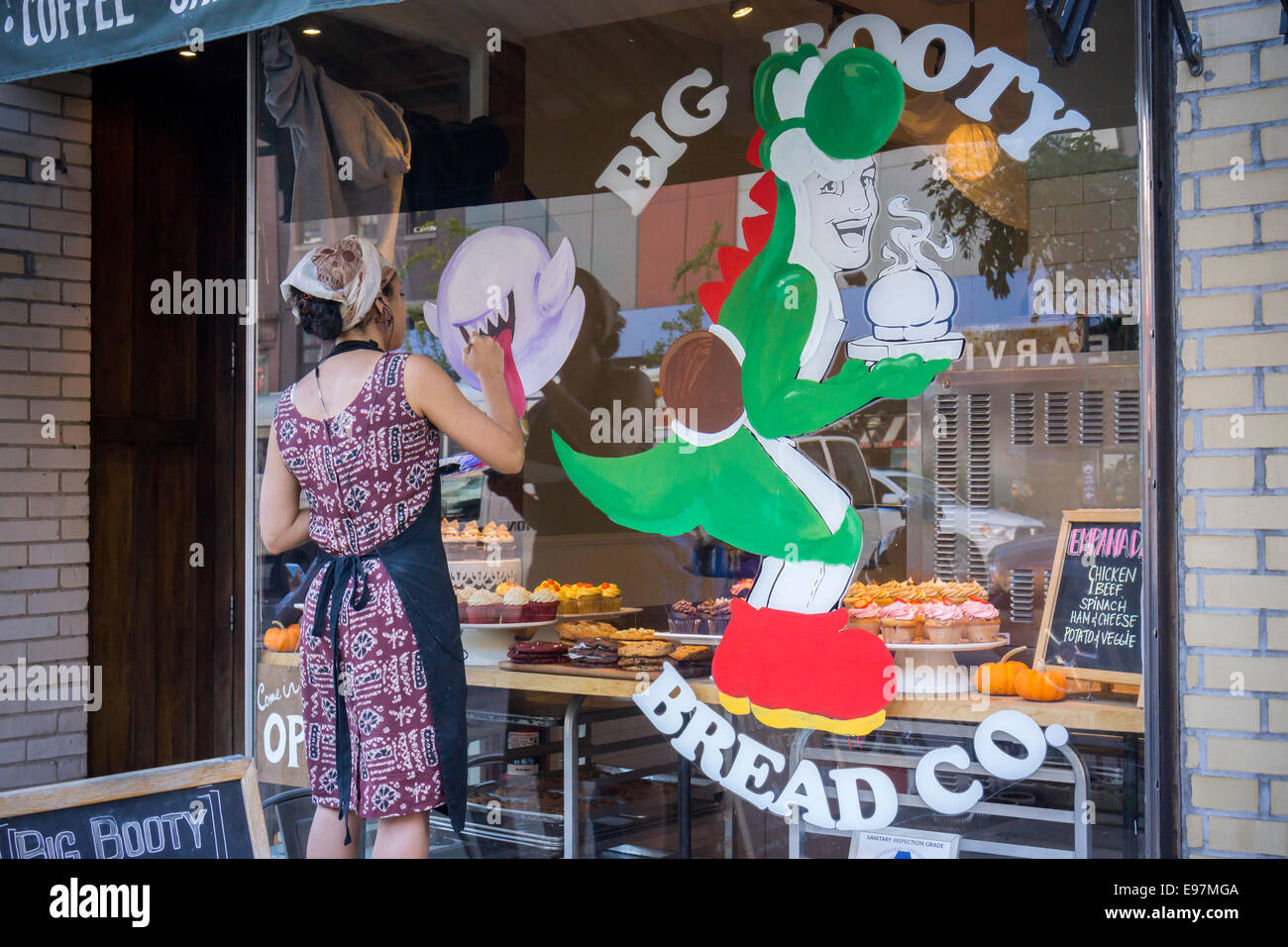 A sign painter decorates the window of the Big Booty Bread Co. bakery in Chelsea in New York - Stock Image