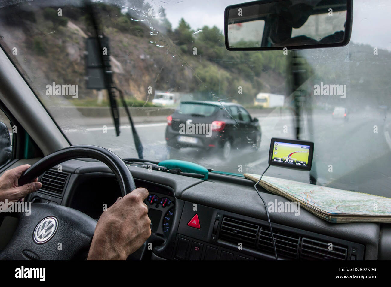 Speeding cars overtaking vehicle on highway during heavy rain shower seen from inside of car with GPS and road map - Stock Image