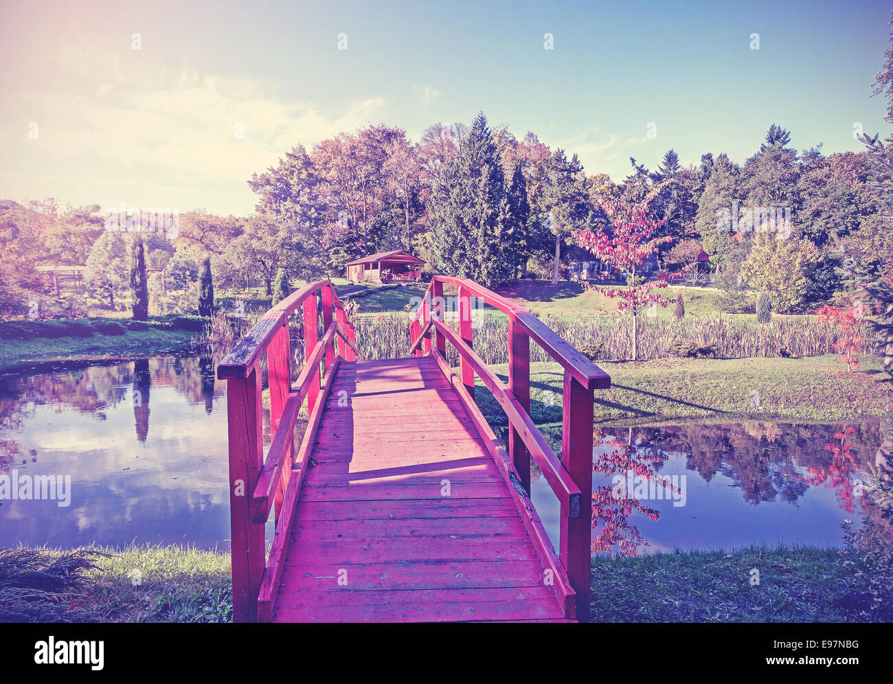 Vintage picture of red bridge in garden. - Stock Image