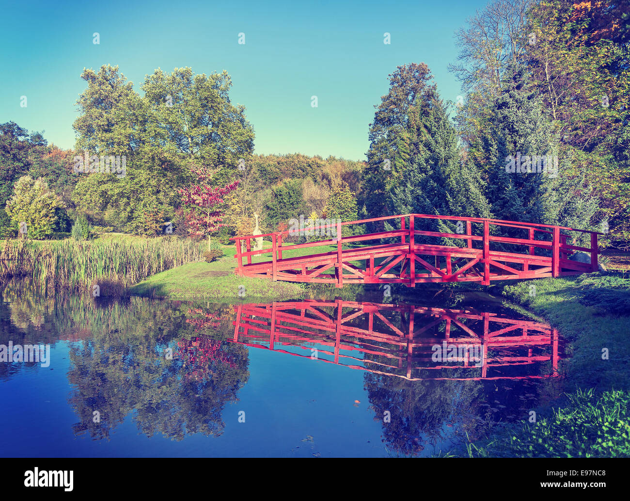 Vintage retro filtered picture of red bridge in garden. - Stock Image
