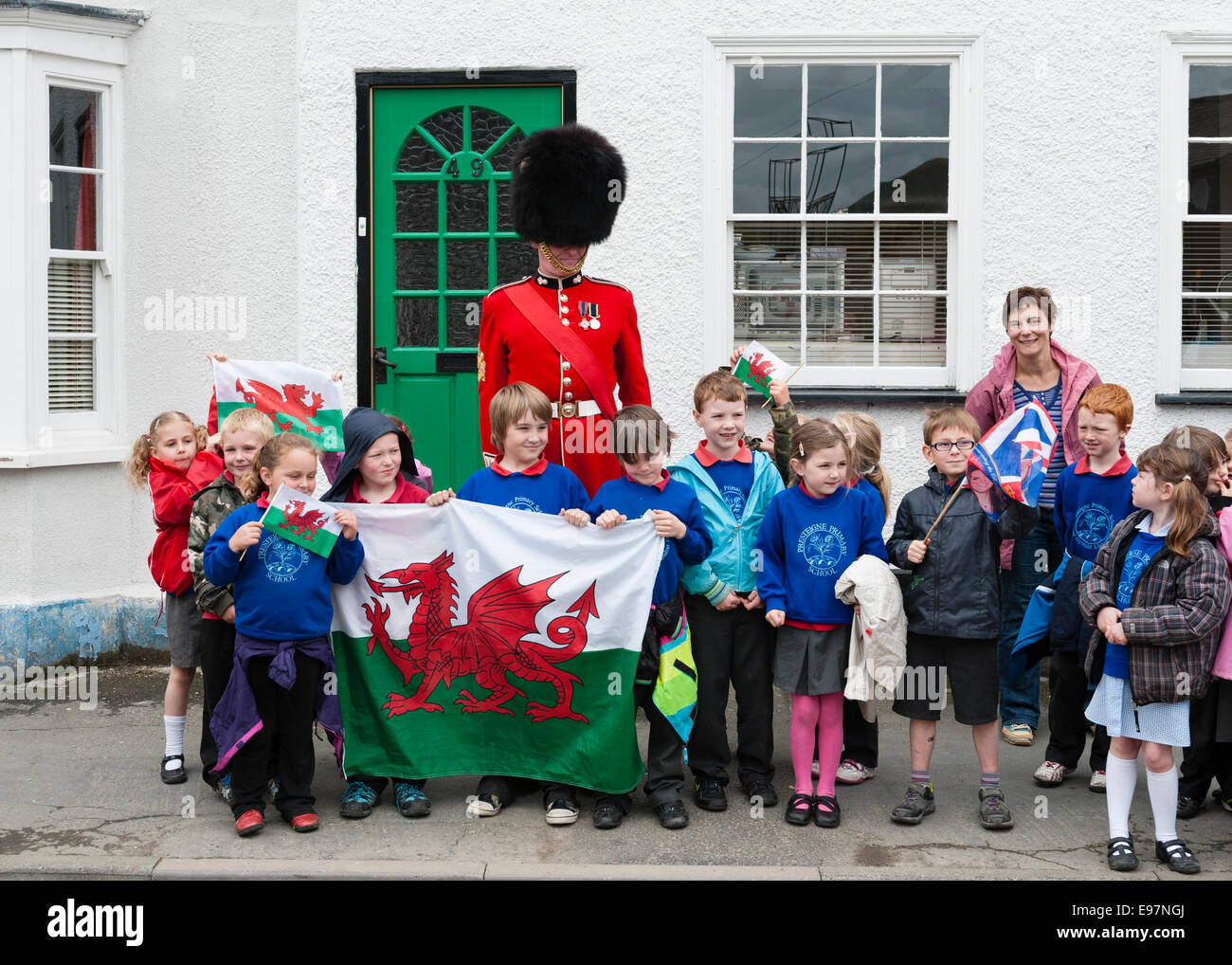 An officer of the Welsh Guards with the children of Presteigne Primary School, Wales, UK - Stock Image