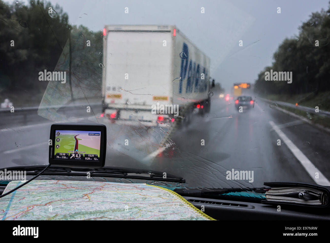 Speeding truck overtaking cars on highway during heavy rain shower seen from inside of car with GPS and road map - Stock Image