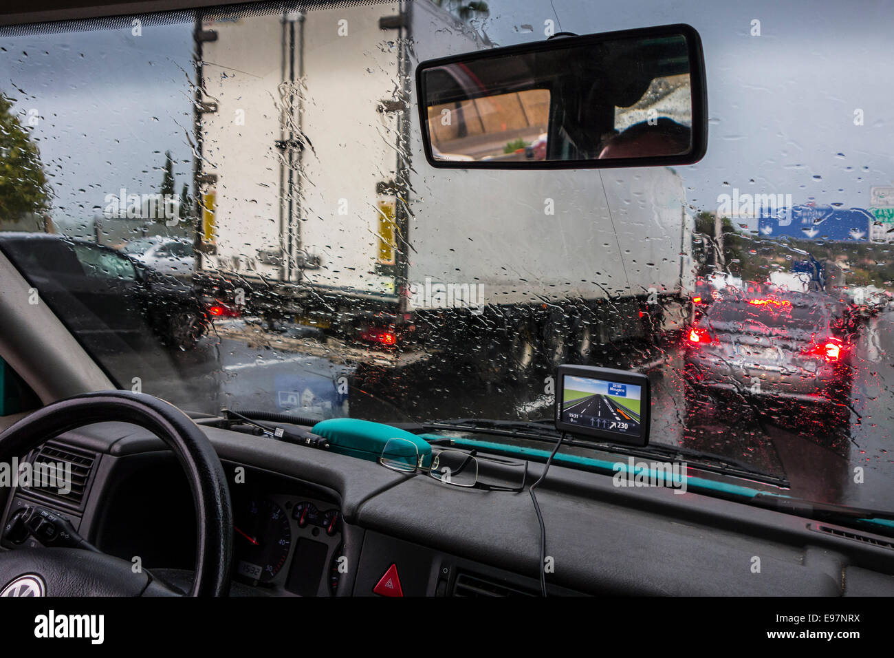 Truck overtaking cars on highway during heavy rain shower seen from inside of vehicle with big raindrops on windscreen - Stock Image