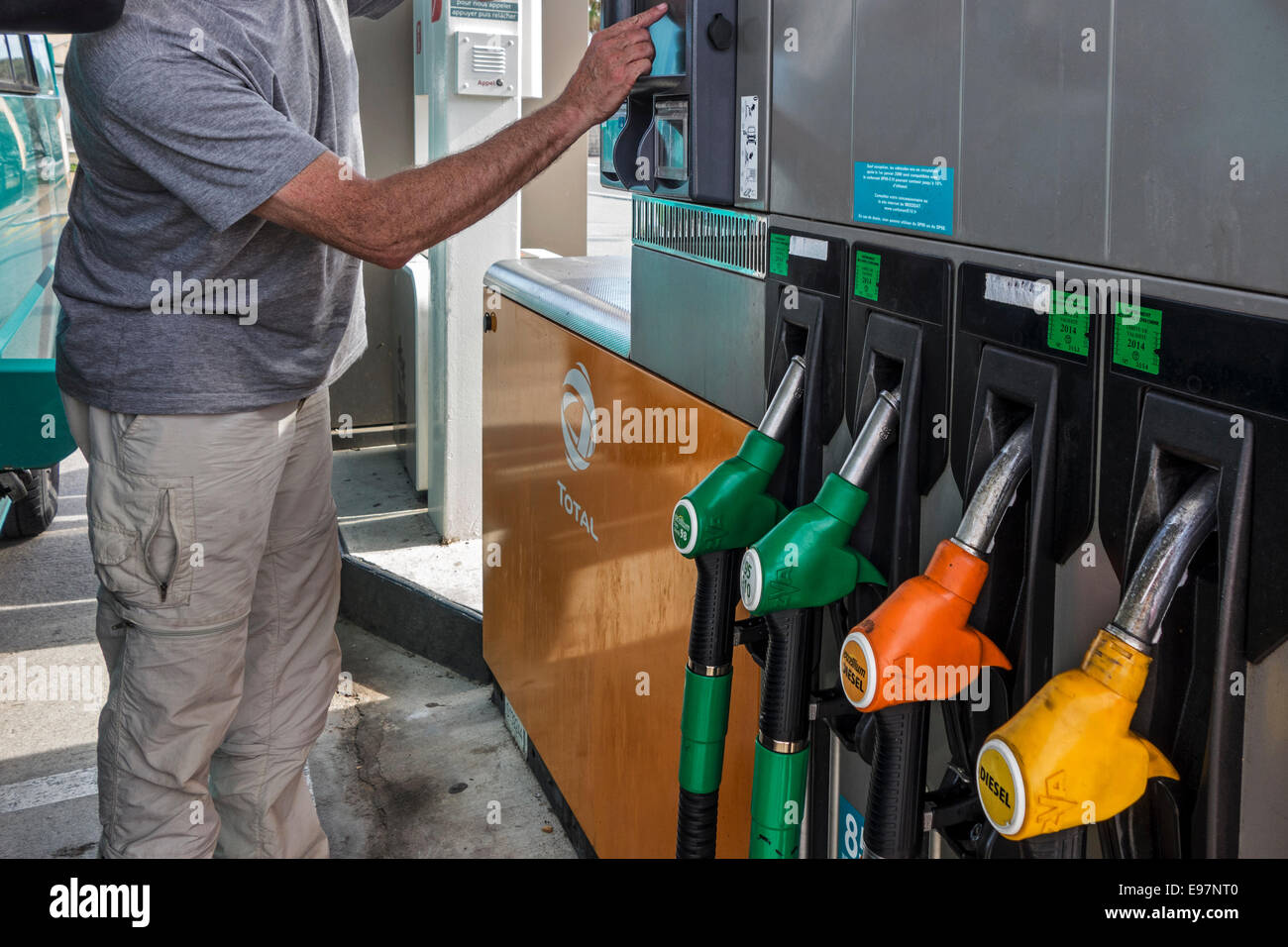 Man selecting fuel pump at Total gas station for refueling his car Stock Photo
