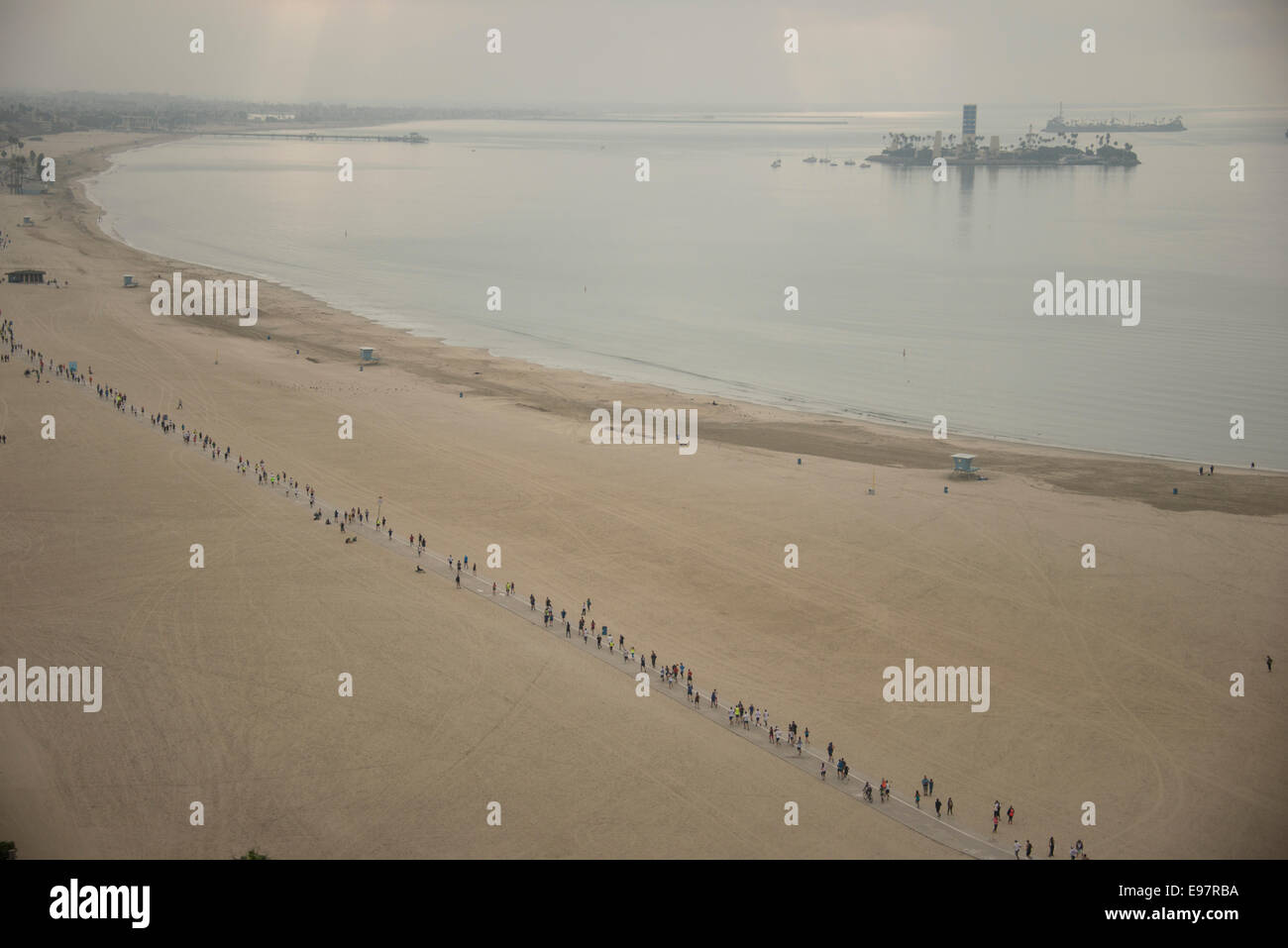 Runners running the Long Beach marathon on path along beach beside Pacific Ocean Long Beach Southern California - Stock Image