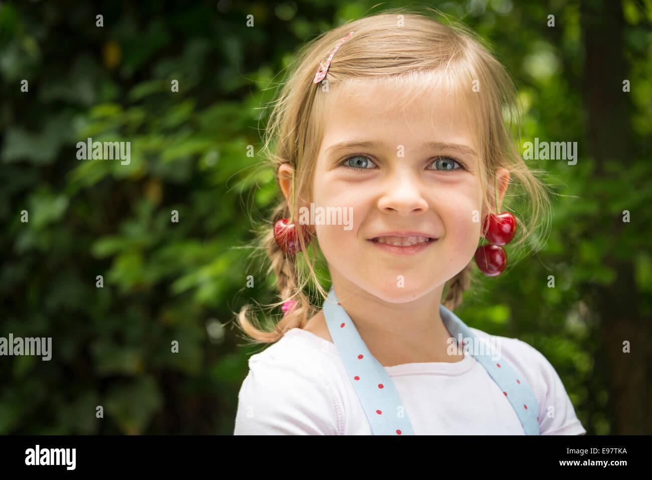 Portrait of little girl, cherries dangling from her ears - Stock Image