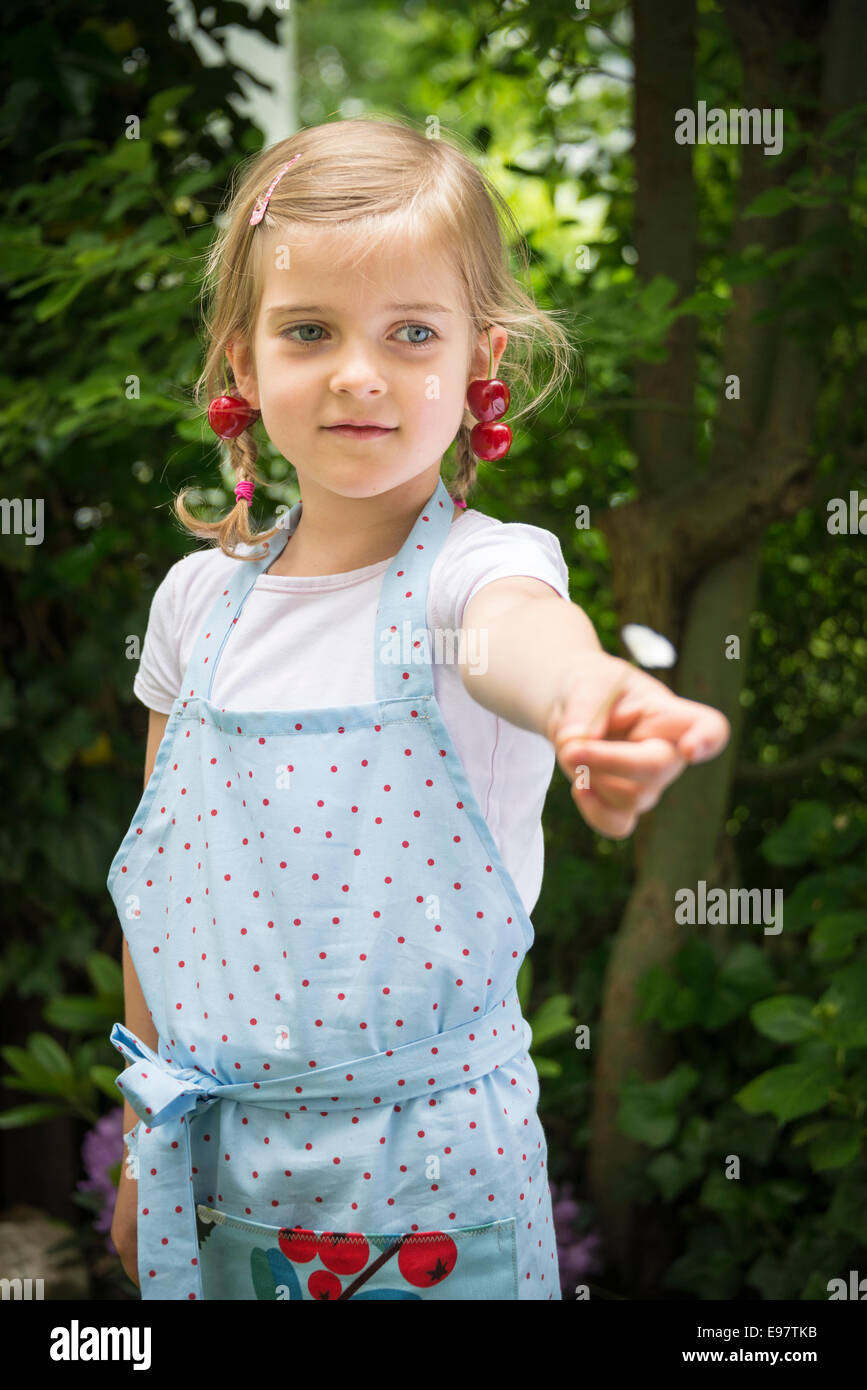 Little girl with cherries dangling from her ears - Stock Image