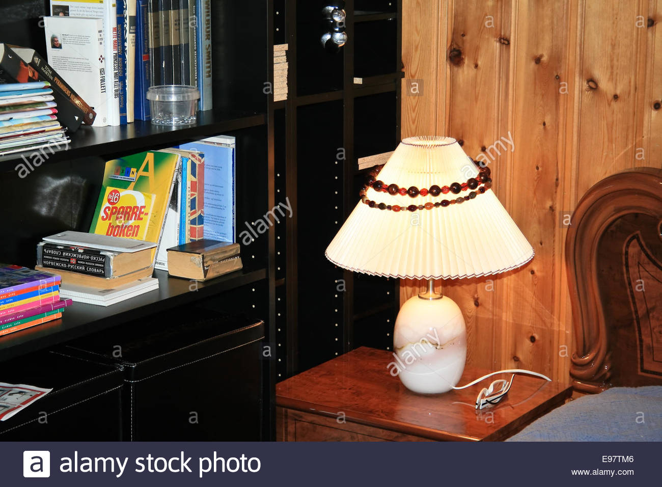 interior room. a lighted lamp on the bedside. shelving of books - Stock Image