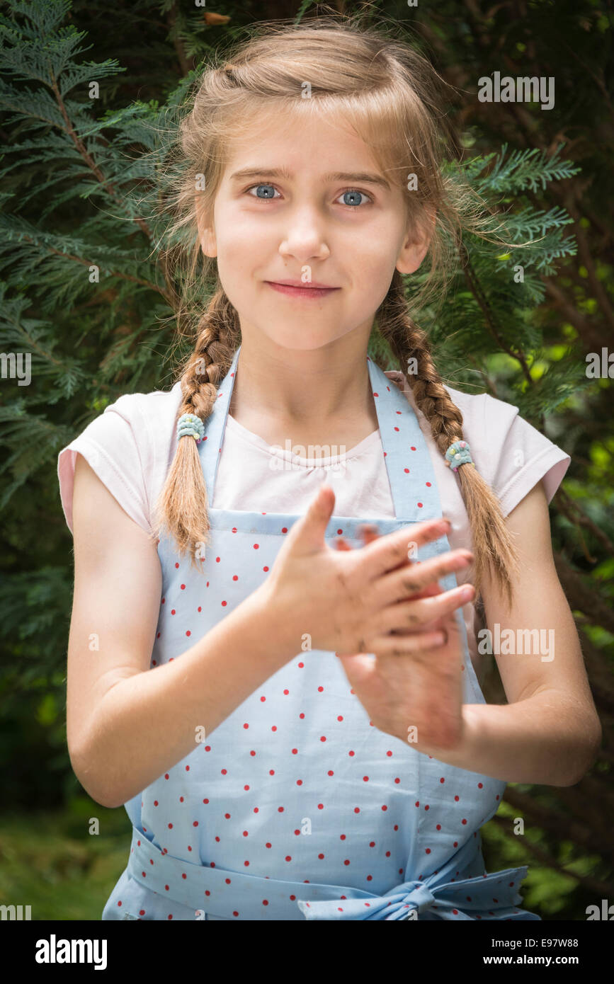 Girl with pigtails gardening, showing her dirty hands - Stock Image