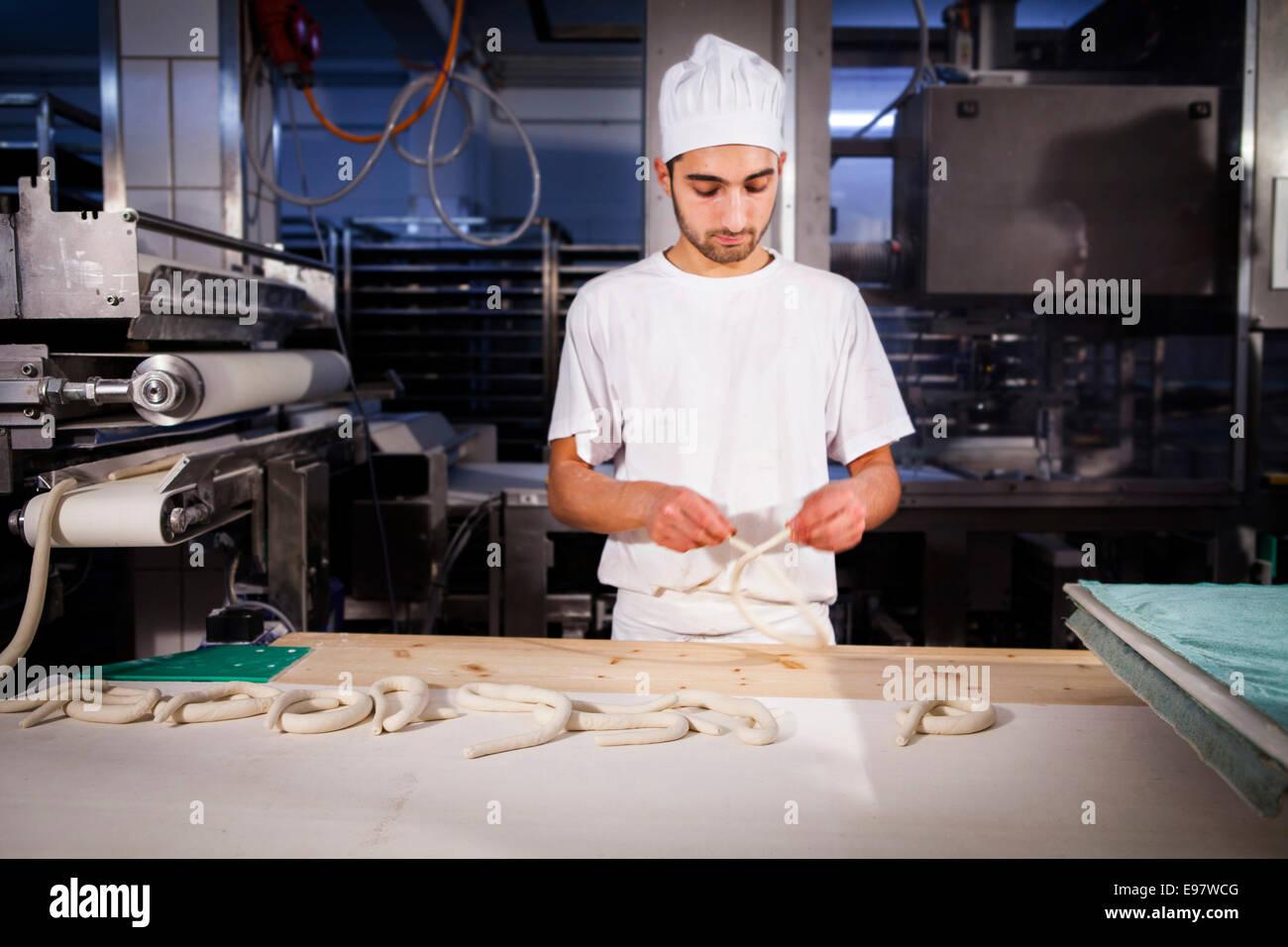 Baker making pretzel dough - Stock Image
