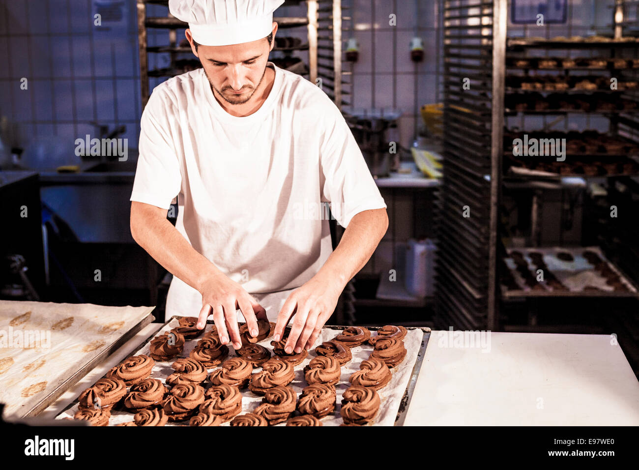 Confectioner positioning chocolate cookies on baking tray - Stock Image