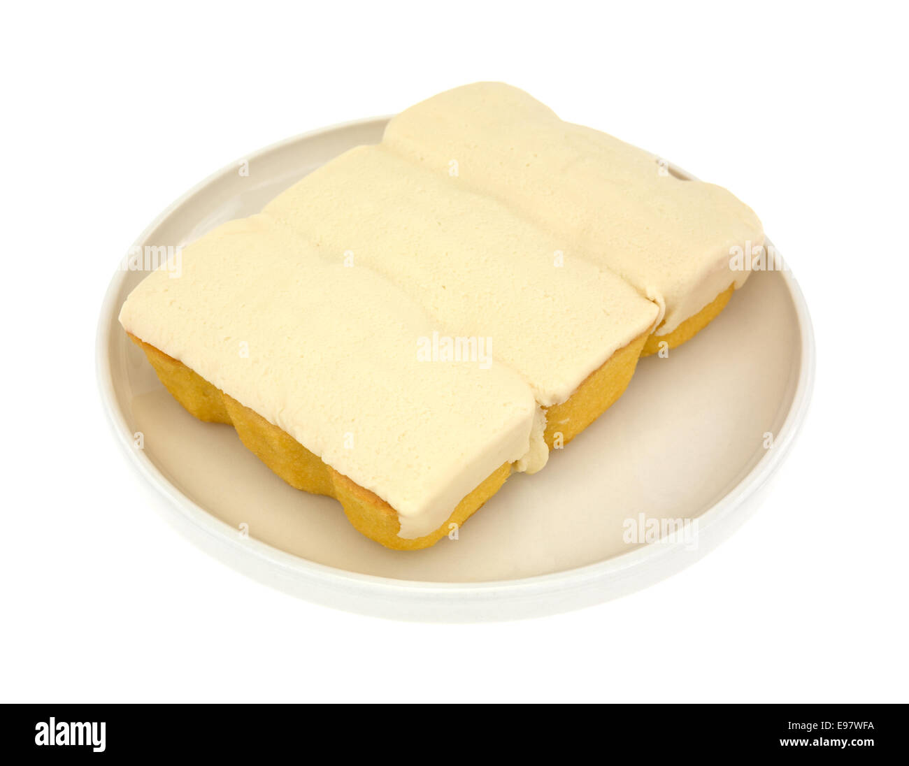 Three small fluffy bite sized snack cakes filled with cream frosting on a plate atop a white background. - Stock Image