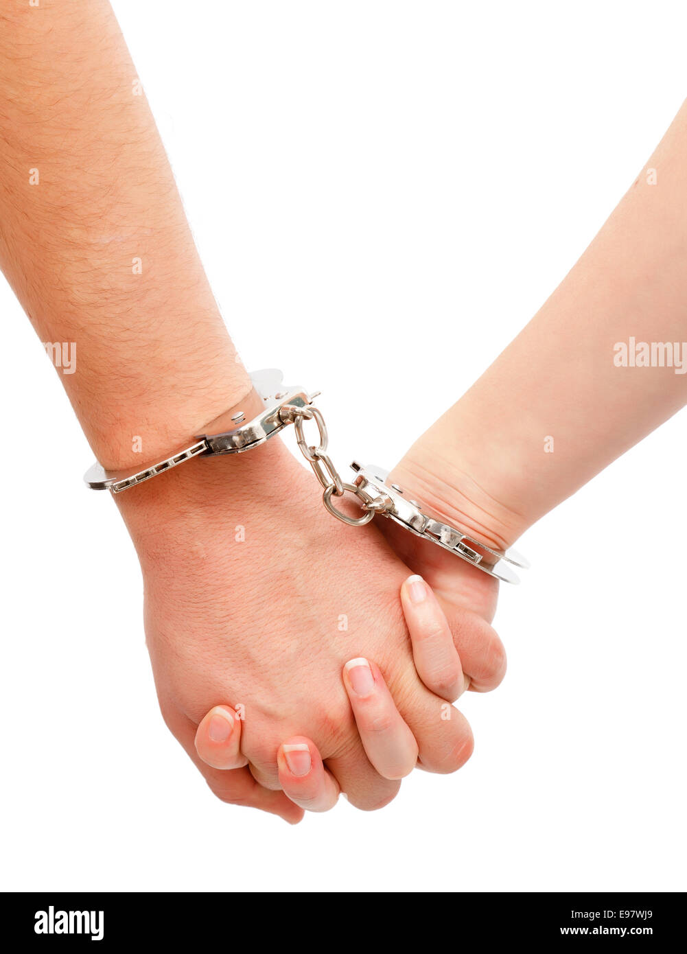 Couple's strong relation metaphor, hands linked with handcuffs - Stock Image