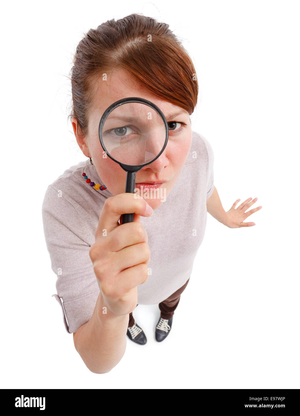 Casual young woman looking through magnifier lens as detective, analyzing or finding something - Stock Image