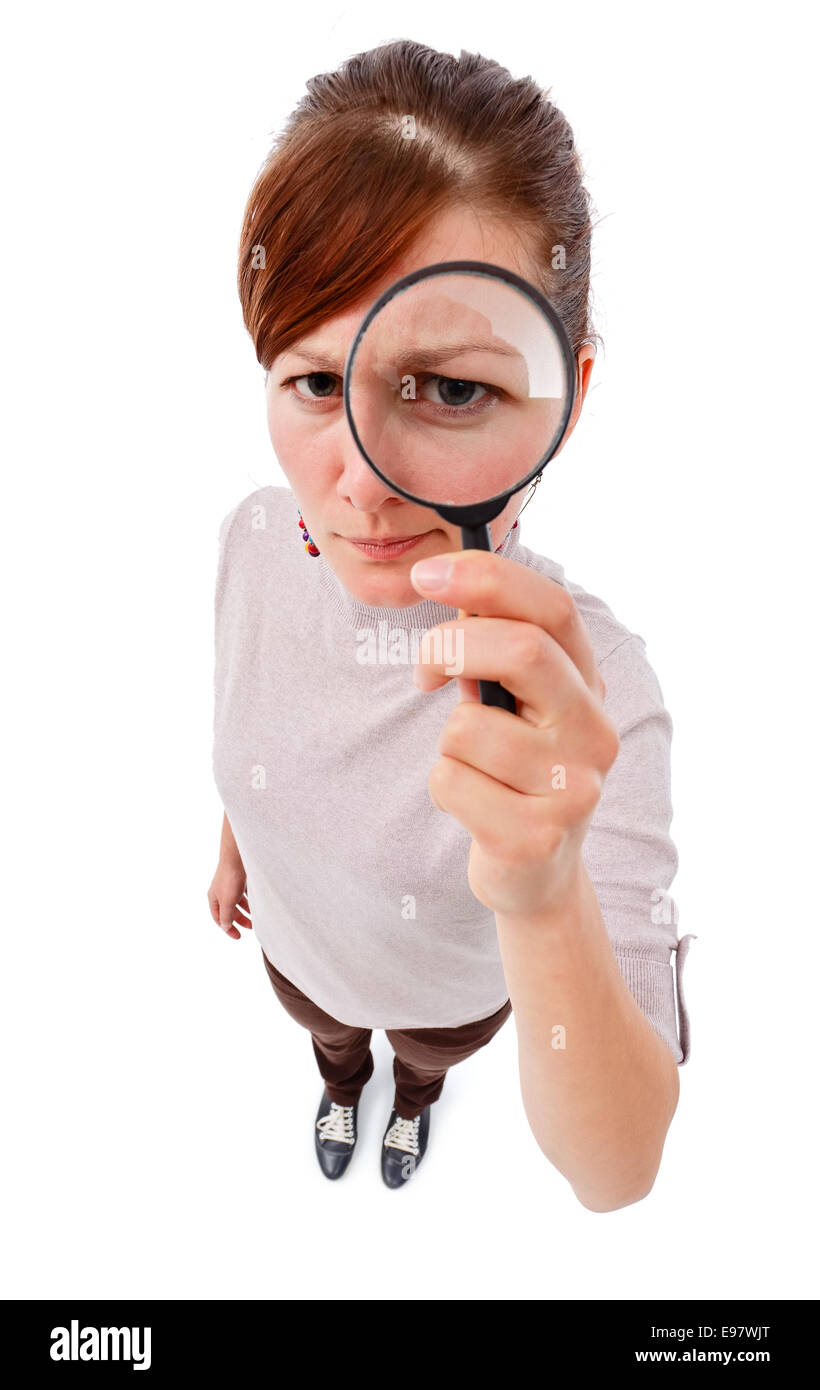 Serious young woman looking through magnifier lens as detective, analyzing or finding something - Stock Image