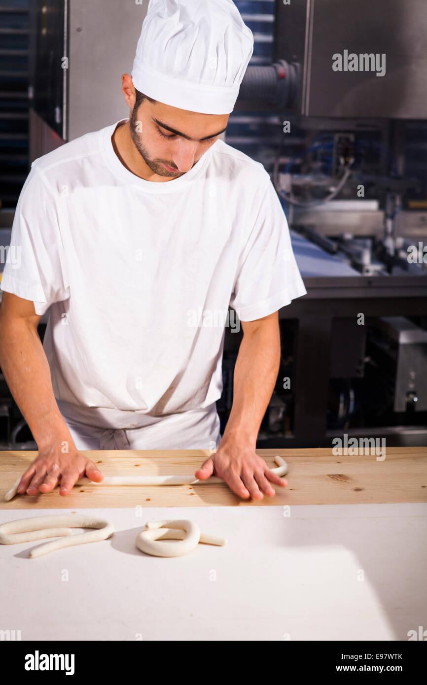 Baker shaping pretzel dough in bakery - Stock Image