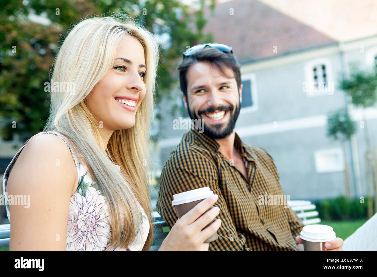 Happy young couple with disposable cups in hands - Stock Image