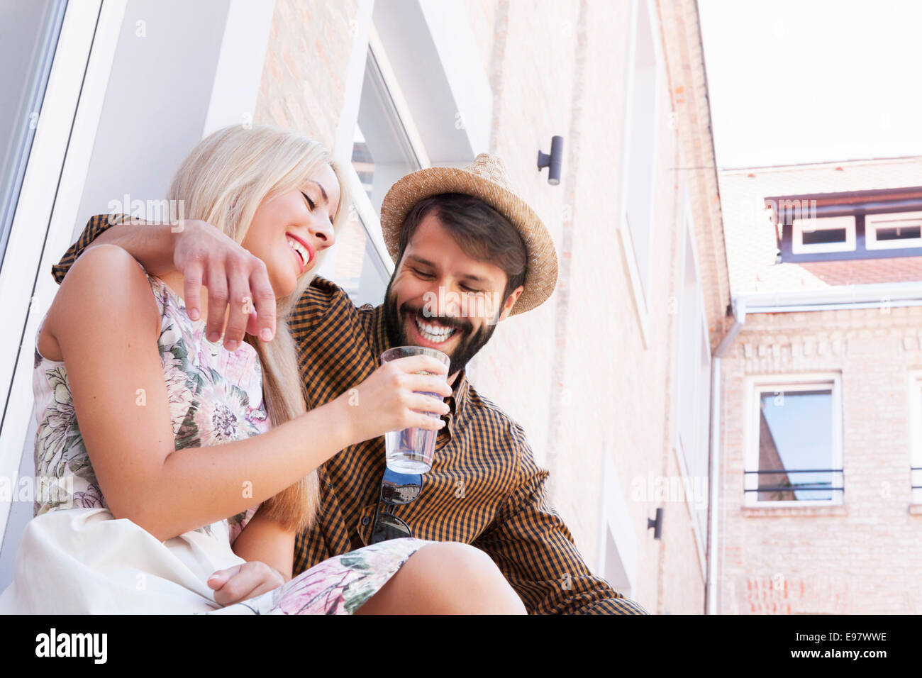 Happy young couple drinking a mineral water together - Stock Image