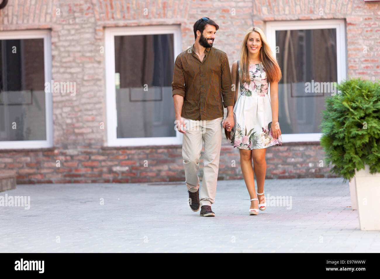 Happy young couple takes a walk holding hands - Stock Image