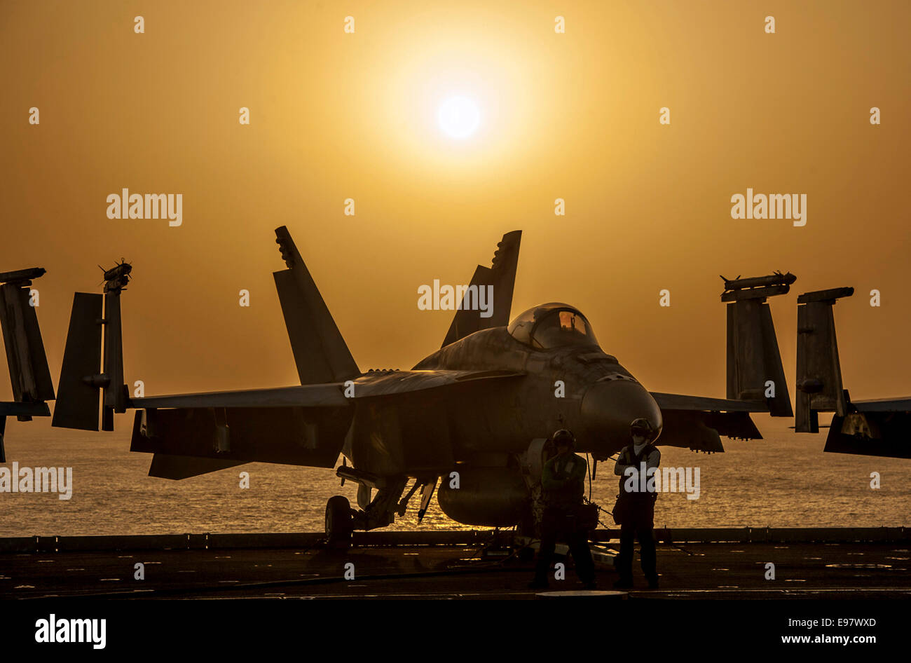 A US Navy F/A-18E Super Hornet fighter aircraft is silhouetted by the setting sun on the flight deck of the aircraft Stock Photo