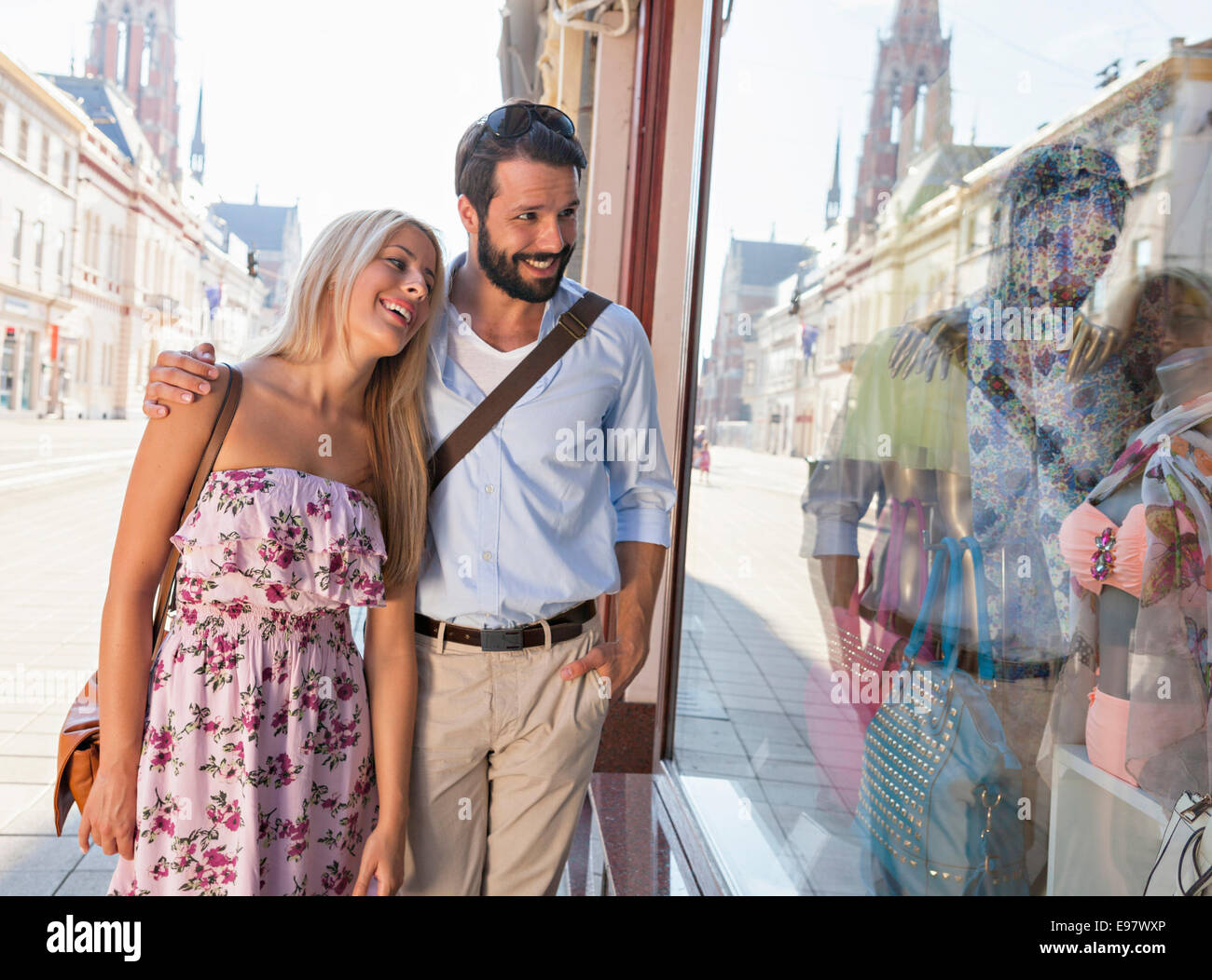 Young couple looking in fashion shop window - Stock Image