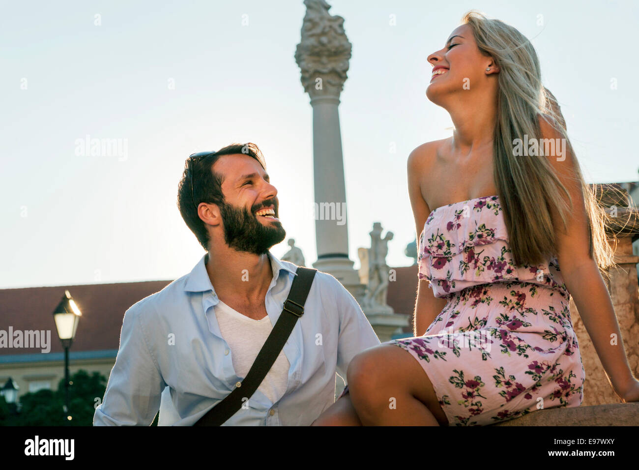 Young couple flirting and laughing by pillar in town - Stock Image