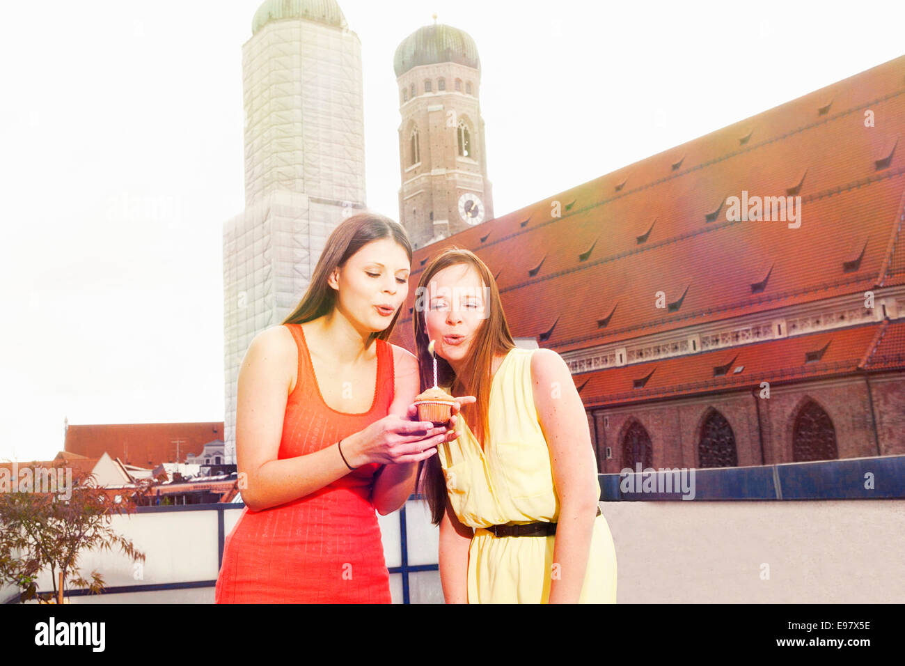 Two young women blowing candle on roof terrace, Munich, Bavaria, Germany - Stock Image
