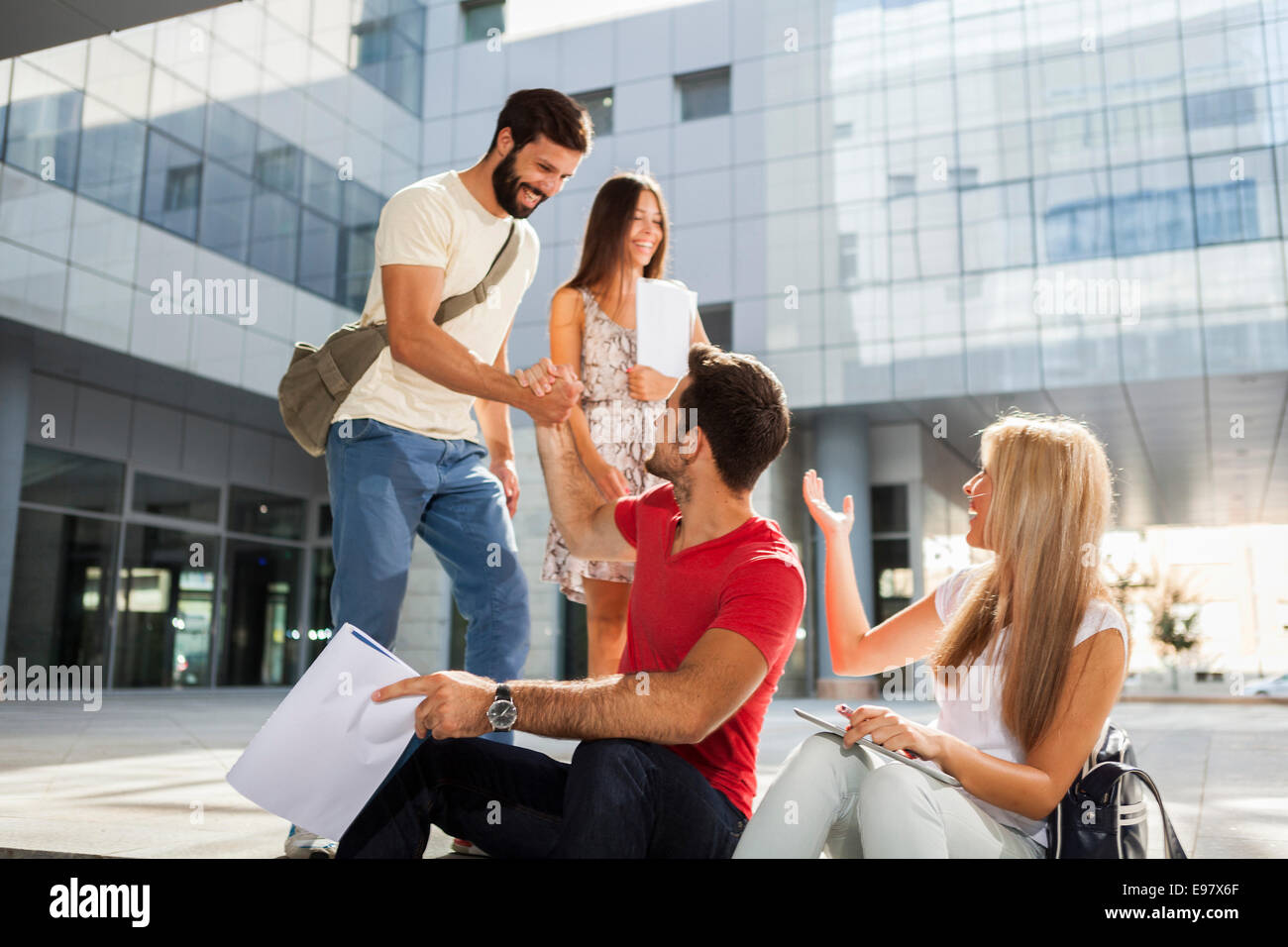 Male students shaking hands on campus grounds - Stock Image