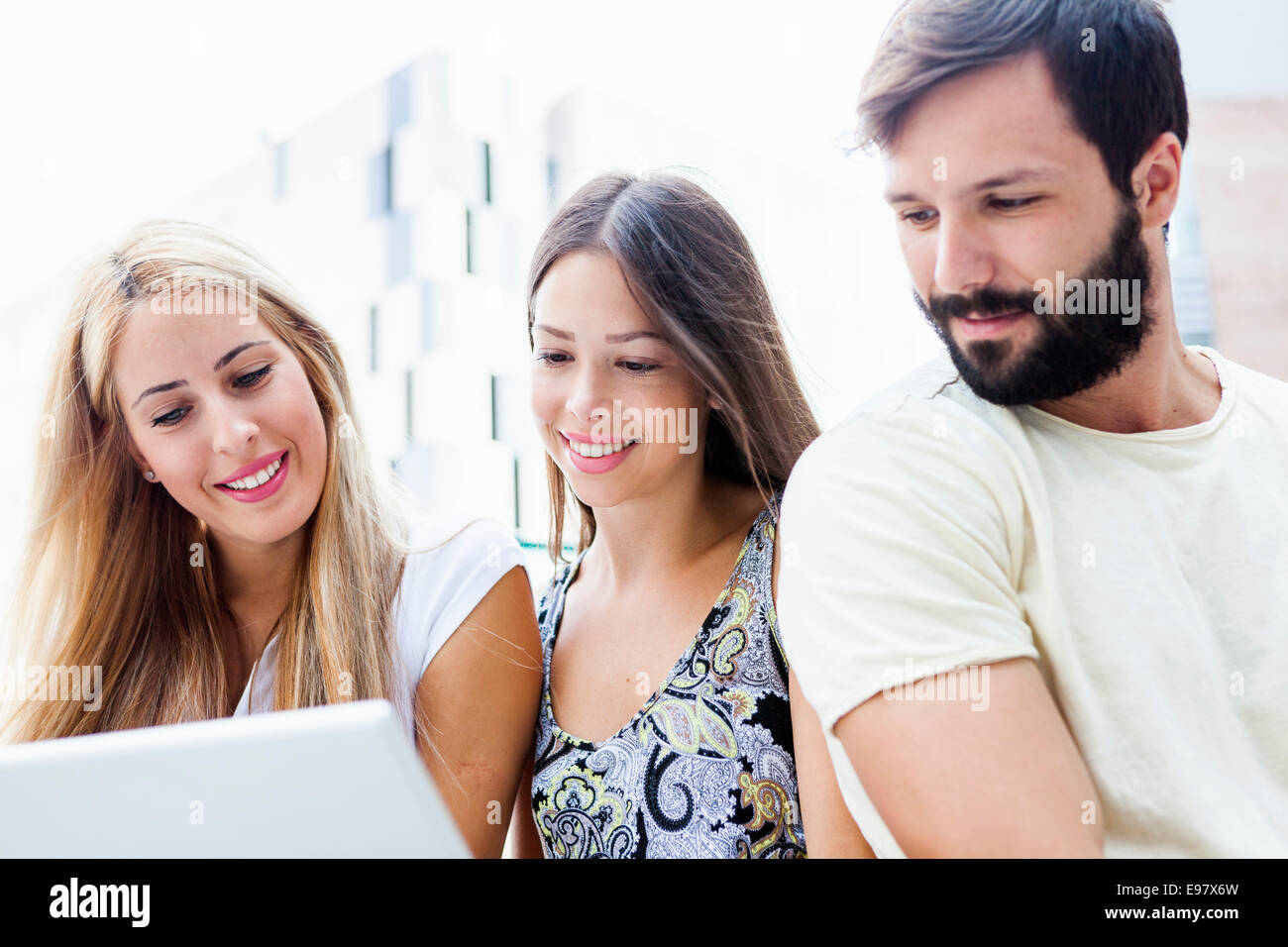 Three students using laptop together - Stock Image