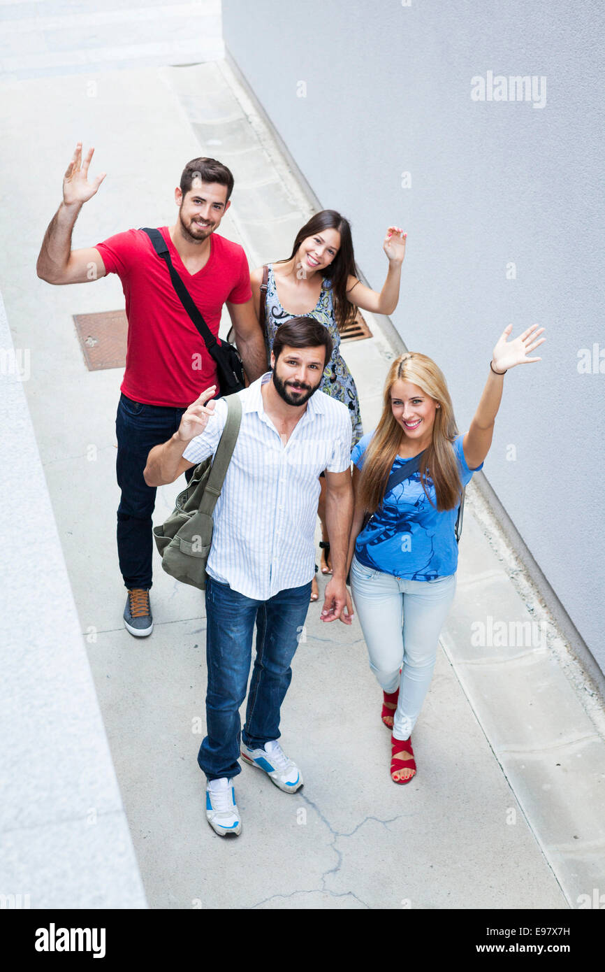 Group of university students waving on campus - Stock Image