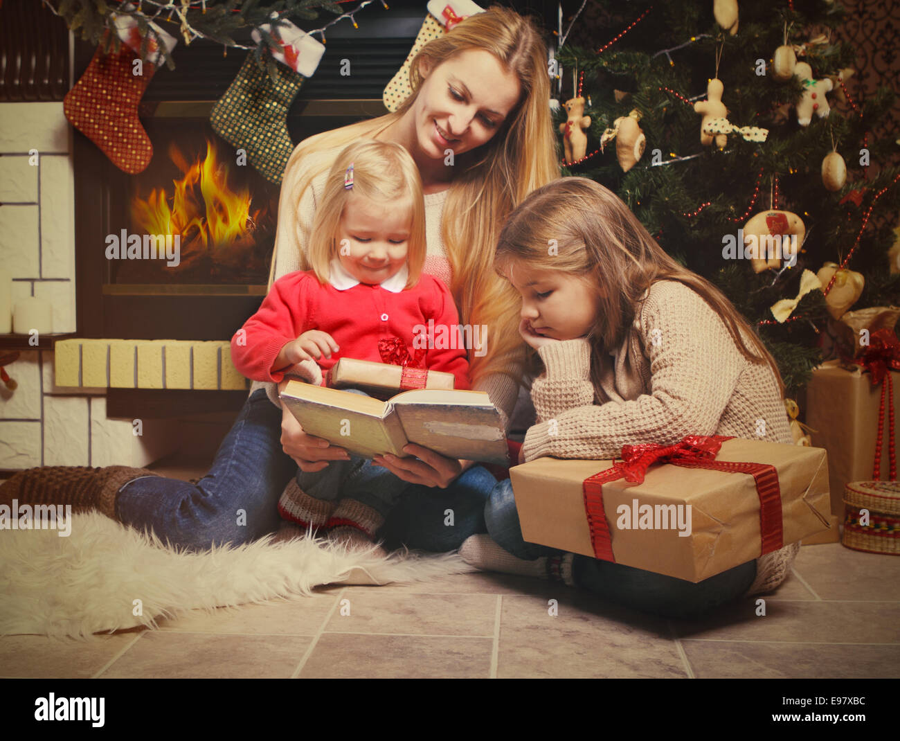 Young mother and her two little daughters with Christmas gifts Stock ...