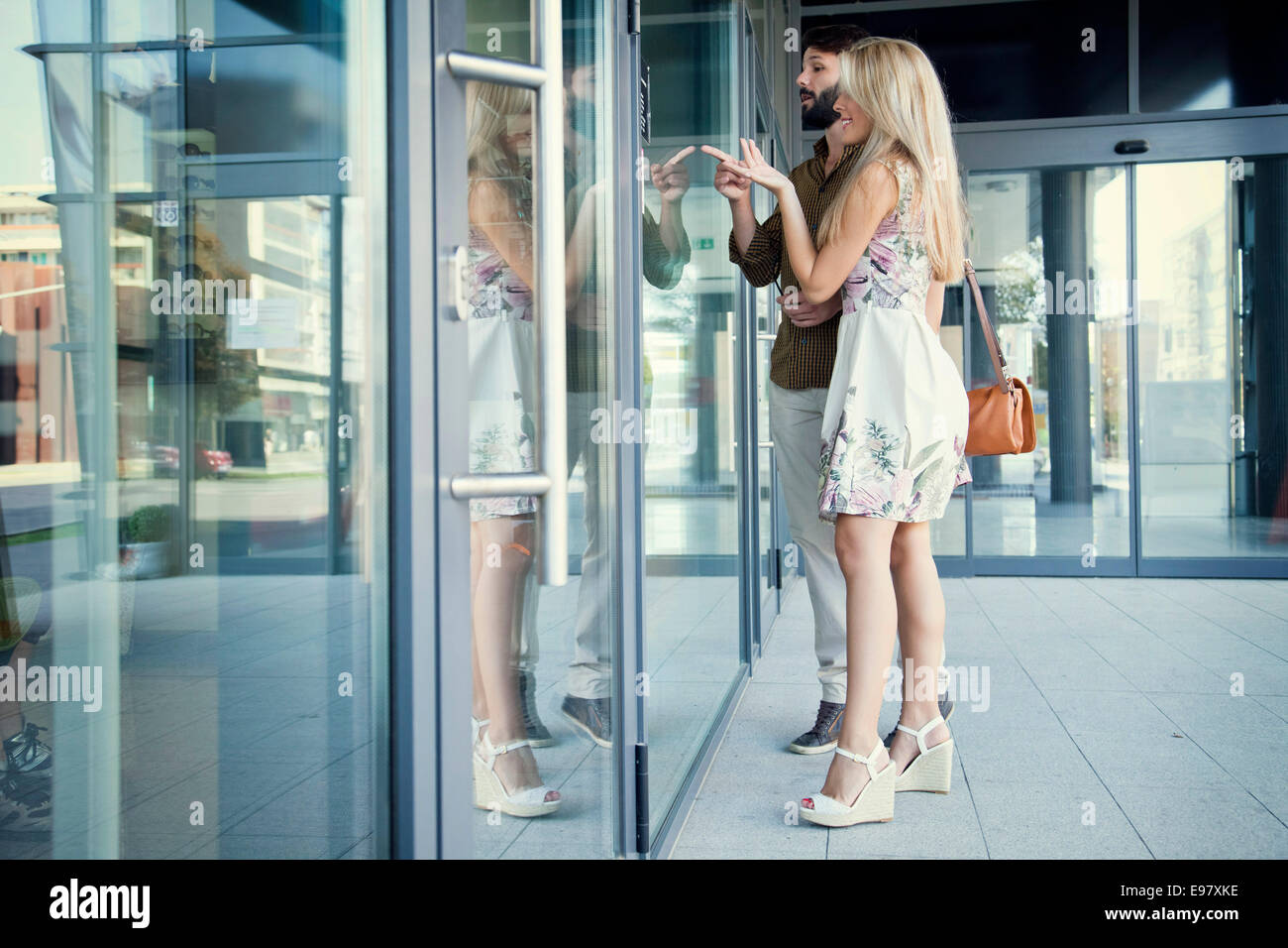Young couple looking and pointing at store window - Stock Image