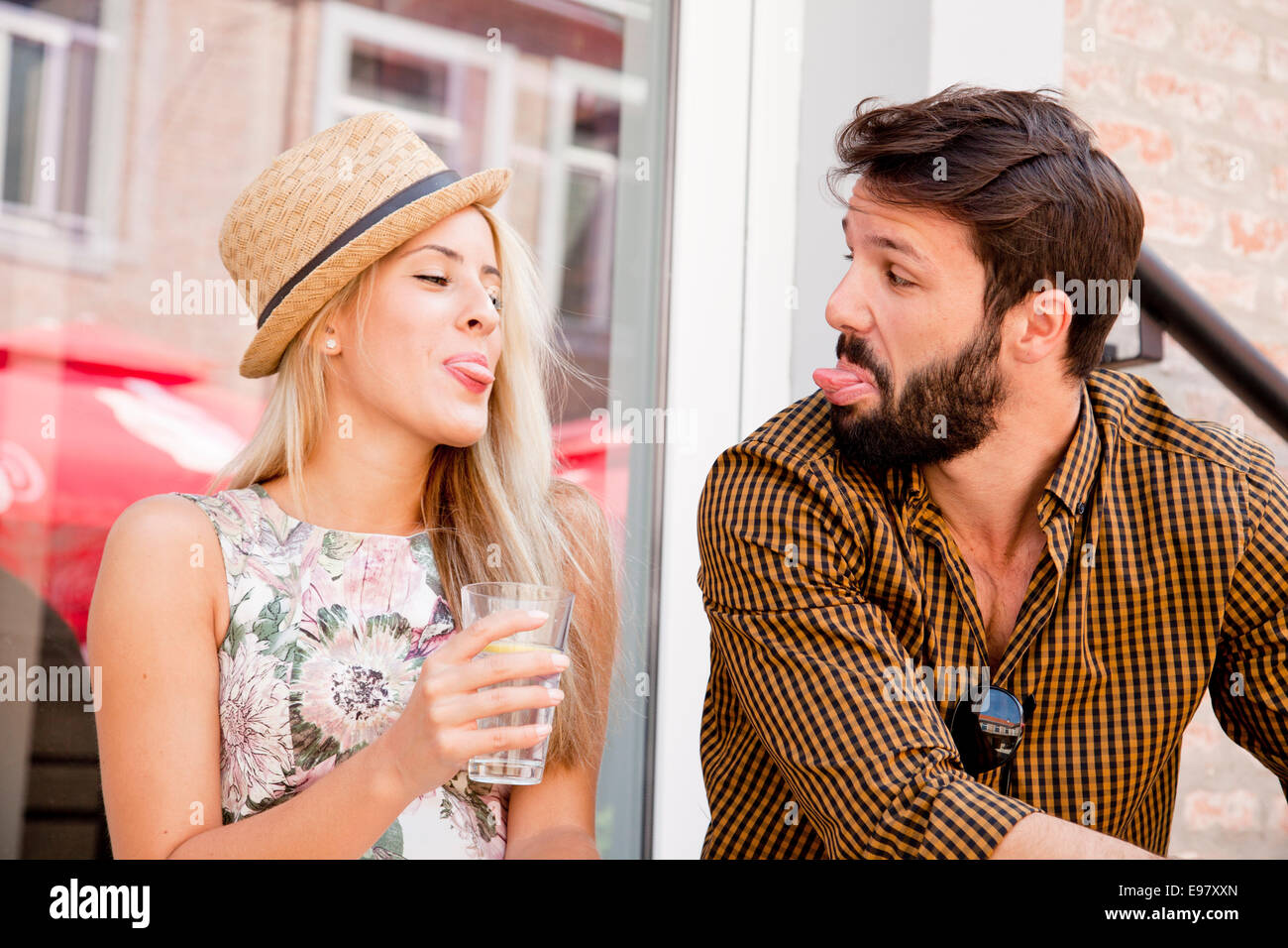 Happy young couple sticking out tongues - Stock Image