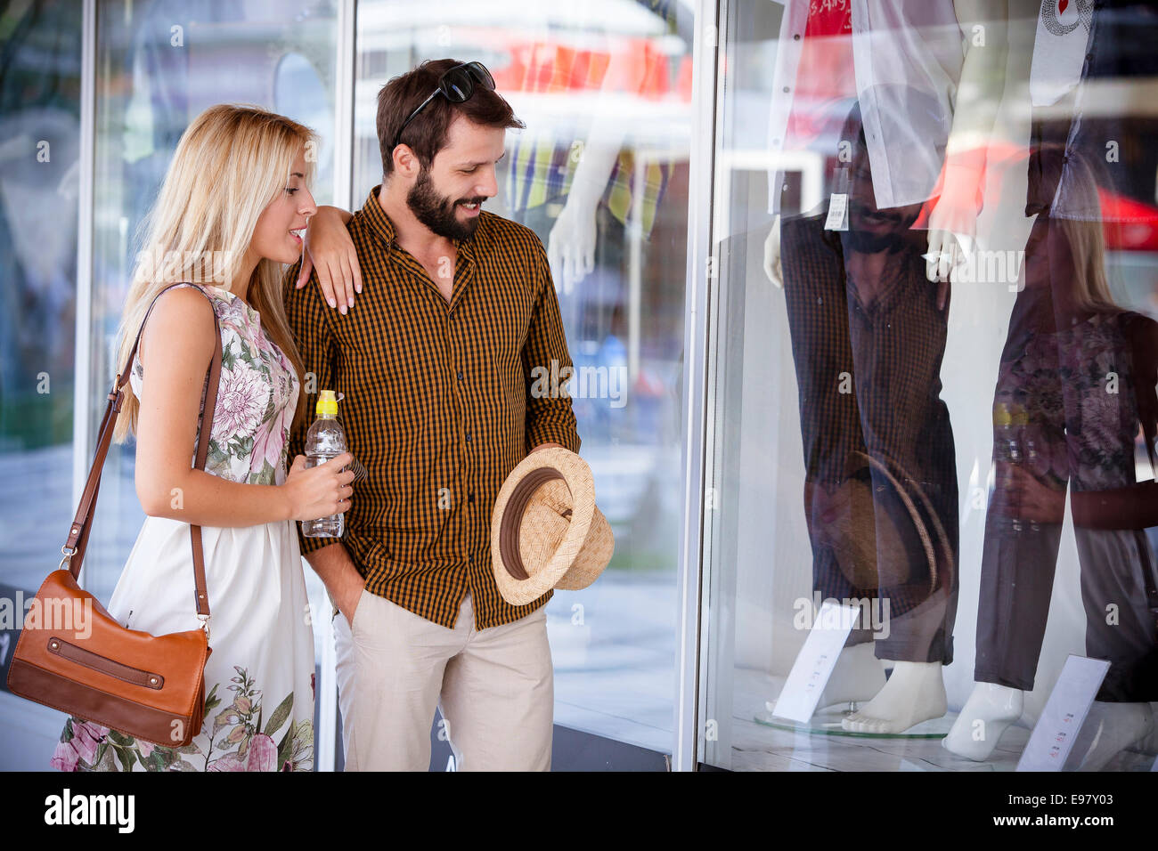 Young couple looking at fashion shop window - Stock Image