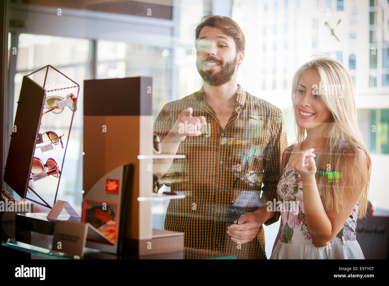Young couple looking through shop window - Stock Image