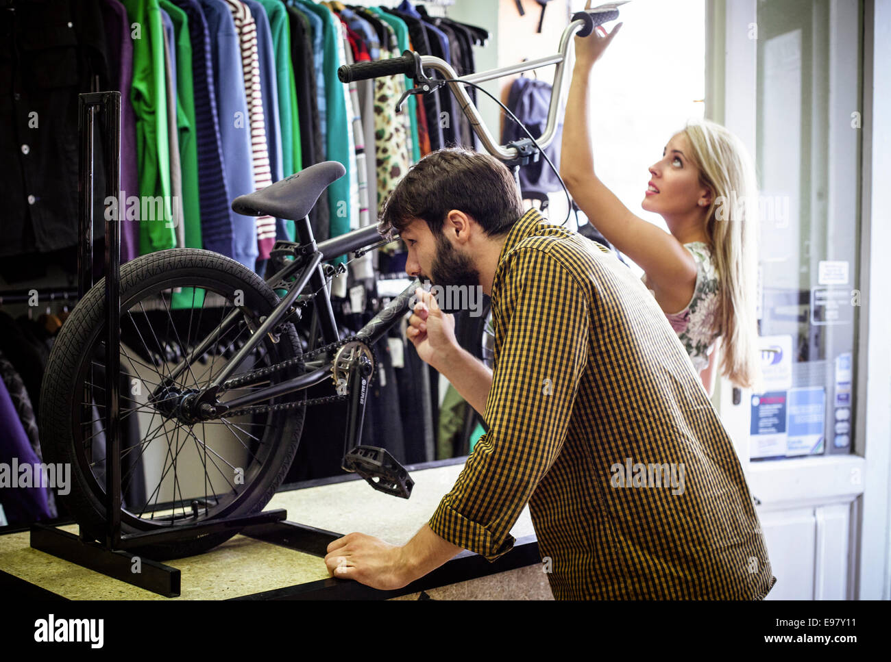 Young couple in bicycle shop looking at bike Stock Photo